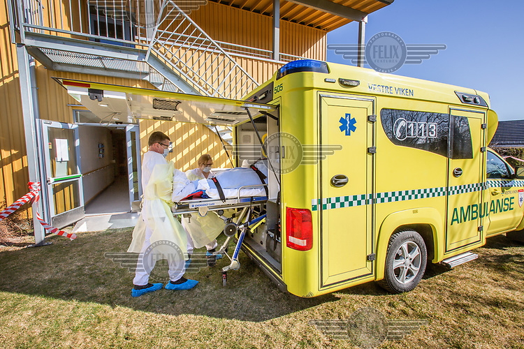 Paramedics in the city of Drammen wearing personal protective equipment (PPE) while transporting patients during the Covid-19 , coronaviraus, pandemic.<br /> <br /> <br /> ©Fredrik Naumann/Felix Features