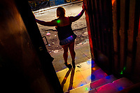 A Salvadoran sex worker, standing in the door, attracts customers to a sex club in San Salvador, El Salvador, 25 November 2018. Sex workers' task in the club is to be an entertaining and seductive companion. Performing erotic dance on the pole they make the customers stay as long as possible and buy relatively expensive alcoholic beverages from which they have a certain share. Sex workers are not obliged to have sexual intercourse with the club customers, they decide themselves, usually according to their current economic situation.
