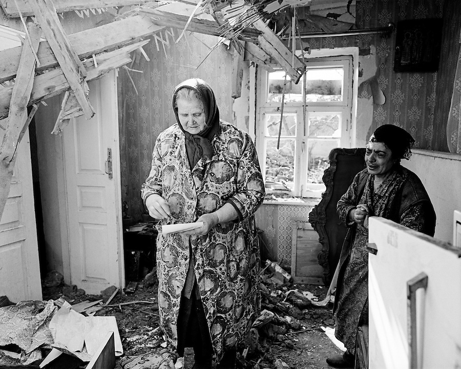 Grozny, Chechnya, March 1995..A Russian woman sifts through the ruined home of a Chechen neighbour whose husband has been killed in the bombardment..