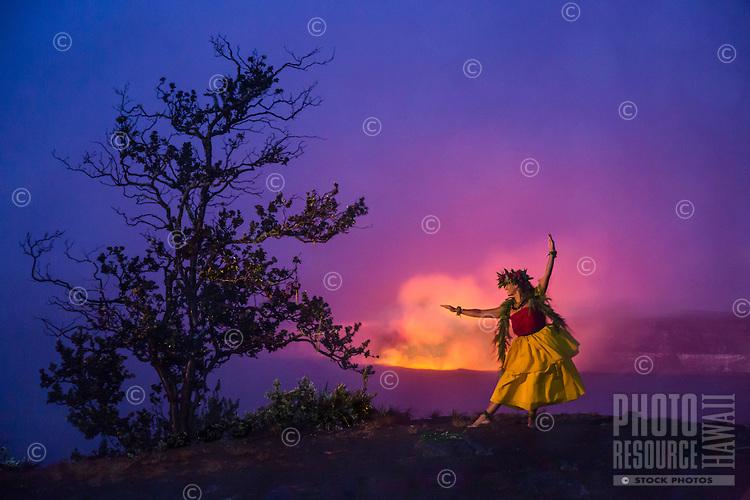 At dusk, a Hawaiian hula dancer in traditional attire dances in honor of the goddess Pele at Halema'uma'u Crater, Island of Hawai'i.