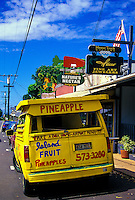 A big yellow island fruit/pineapple van is parked near galleries and shops in the cowboy town of Makawao, just below the Haleakala Ranch.