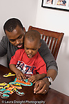 2 year old toddler boy playing with puzzle assisted by father vertical African American