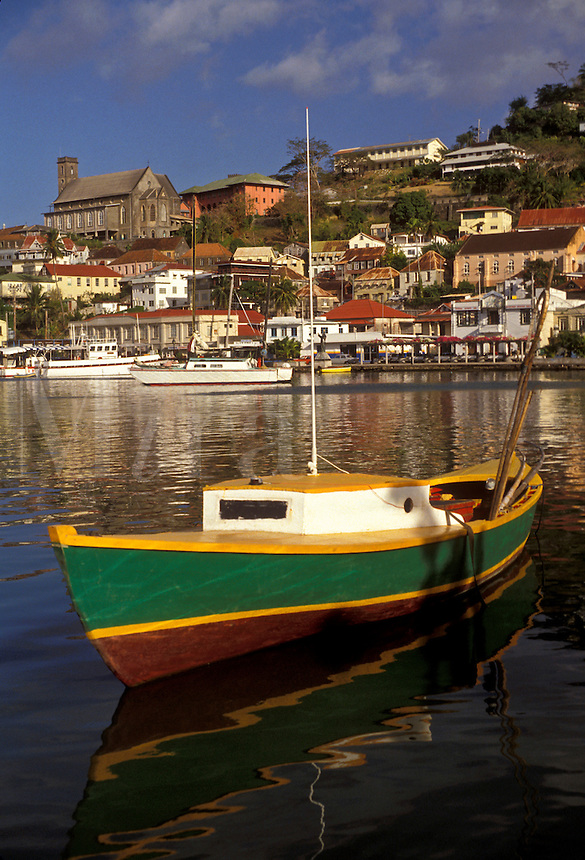 """AJ2529, Grenada, Caribbean, St. George's, Caribbean Islands, Green fishing boat anchored in the calm waters of the harbor with a scenic view of St. George's the capital city on the island of Grenada """"""""the spice isle"""""""" (a British Commonwealth member)."""