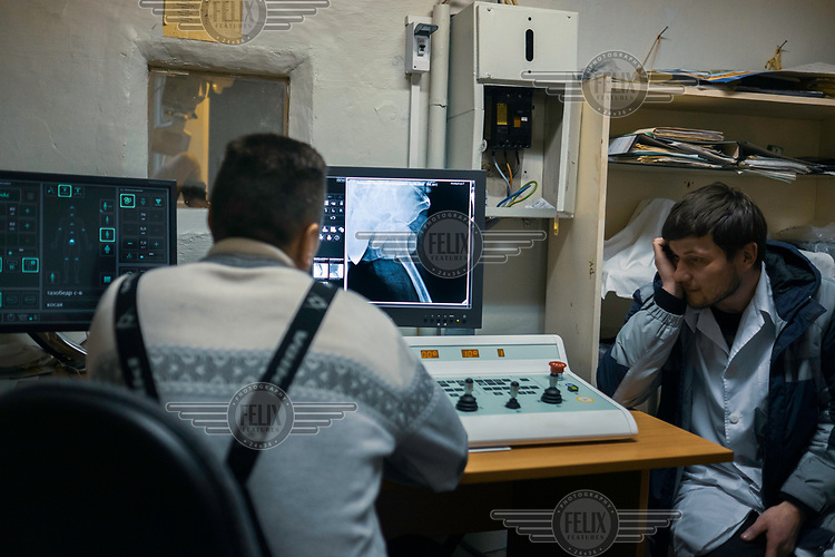 Radiologist Stanislav and paramedic Alexey check an x-ray of a patinet's broken leg at the hospital.