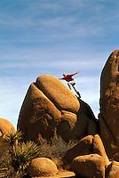 Woman climbing / balancing on a Rock, Joshua Tree National Park, California, USA (Model Released)