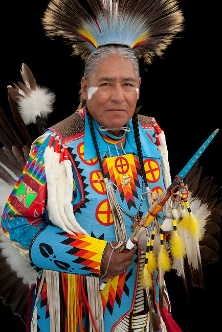 Norman Largo (Dine aka Navajo) dressed in colorful men's traditional dance clothing and roach headdress holds an eagle wing fan and beaded dance stick