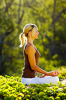 A young woman meditates in Makena, Maui.