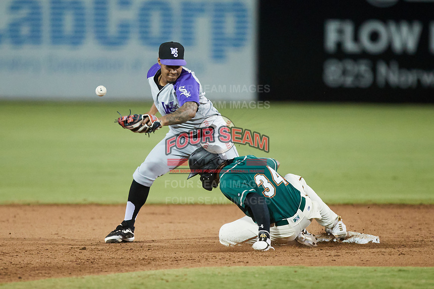 Lolo Sanchez (34) of the Greensboro Grasshoppers slides into second base as Yolbert Sanchez (2) of the Winston-Salem Dash tries to receive a throw at First National Bank Field on June 3, 2021 in Greensboro, North Carolina. (Brian Westerholt/Four Seam Images)
