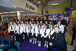 Only Men Aloud male voice choir singing the Welsh national anthem with a local school choit at the Tesco Extra store in Fforestfach, Swansea today where they performed live before signing copies of their new CD which was released today..