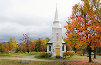 White church in fall foliage.St Matthews Episcopal Church in Sugar Hill, New Hampshire