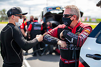 Jul 12, 2020; Clermont, Indiana, USA; NHRA funny car driver Tommy Johnson Jr (right) and Jonnie Lindberg greet each other with a fist bump and elbow tap during the E3 Spark Plugs Nationals at Lucas Oil Raceway. This is the first race back for NHRA since the start of the COVID-19 global pandemic. Mandatory Credit: Mark J. Rebilas-USA TODAY Sports