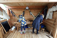 Friday 23 May 2014, Hay on Wye UK<br /> Pictured: Two women having a go at wood working.<br /> Re: The Telegraph Hay Festival, Hay on Wye, Powys, Wales UK.