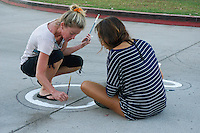 Mission Bay High School, San Diego CA, USA.  Saturday, October 10th 2015:  Mission Bay High School Art Teacher Heather Henkes (L) works with a student and community members to paint a street mural in front of the High School Gym.  The mural installation was funded by the non-profit organization Beautiful PB through a grant from SANDAG.