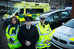 © Joel Goodman - 07973 332324 . 19/12/2014 .  Manchester , UK . Paramedic Jo Hodson , Undertaker Leyton Moores and Police Sergeant John Brennan . Emergency services photocall in Manchester City Centre , ahead of Mad Friday night , featuring an ambulance , a police car and a hearse , highlighting the travel options some revellers will face after a night out . Police say a hundred police will be patrolling in Manchester City Centre this evening (Friday 19th December) after previous reports have said as few as four have been available some nights . Photo credit : Joel Goodman/LNP
