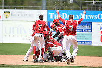 Batavia Muckdogs outfielder Victor Castro (40) is mobbed by teammates including Mason Davis (7), Luis Alberto Sanz (19), Miles Williams (26), Kevin Grove (12) and Ryan Aper (3) after a walk off single during a game against the Lowell Spinners on July 17, 2014 at Dwyer Stadium in Batavia, New York.  Batavia defeated Lowell 4-3.  (Mike Janes/Four Seam Images)