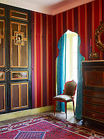 The Renaissance-style doors in a guest bedroom were painted by Gerard Tremolet, the Elizabeth Garouste chair is upholstered in a Lelievre leopard print cotton and the marquetry-inlaid secretaire is Napoleon III
