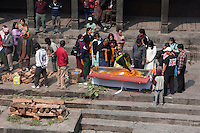 Pashupatinath, Kathmandu, Nepal.  Family Member Places a Wreath of Marigolds and a Letter inside a Coffin of a Deceased, while Wood for the Cremation Pyre Awaits.