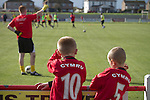 Prestatyn Town 0 Port Talbot Town 0, 19/10/2013. Bastion Gardens, Welsh Premier League. Two young fans with the word Cymru, the Welsh word for Wales, on their shirts, watching the players warming up at Bastion Gardens prior to the match between Prestatyn Town and visitors Port Talbot Town in the Welsh Premier League. Prestatyn Town were Welsh Cup winners in 2013. The match ended goalless and was watched by 211 spectators. Photo by Colin McPherson.