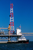An offshore oil drilling rig with a supply boat.