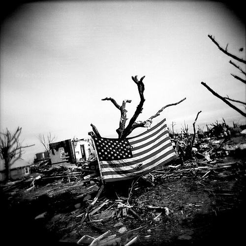 Greensburg, Kansas <br /> USA<br /> June 2007<br /> <br /> An American flag hangs amid the wreckage and debris left by the tornado.  The small town of Greensburg, Kansas was nearly completely destroyed after a mile-wide tornado and winds of 165 mph tore through the area, killing 12 people. Some 90 percent of Grennsburg's homes and businesses were damaged or destroyed in the vicious storm. An American flag is displayed amid the wreckage and debris left in the wake of the tornado.