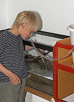 Junge füllt teilweise eingerichtetes Becken mit Wasser auf
