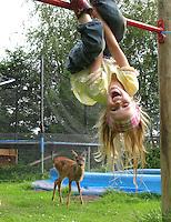 Rehkitz, Reh-Kitz, junges, verwaistes, pflegebedürftiges Tier im Garten zwischen Spielzeug einer Wildtier-Aufzuchtstation, Wildtier-Auffangstation, Wildtierhilfe Fiel, im Vordergrund ein Mädchen, Kind am Reck, Kitz, Tierkind, Tierbaby, Tierbabies, Europäisches Reh, Ricke, Weibchen, Capreolus capreolus, Roe Deer, Chevreuil