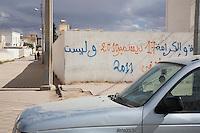 Tunisia, Sidi Bouzid, il dopo Rivoluzione. Un muro dove è scritta la data dell'inizio della Rivoluzione, il 17 dicembre 2010. Lungo il marciapiede due persone e una macchina posteggiata.