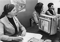 1967 FILE PHOTO - ARCHIVES -<br /> <br /> Beauty Redoubled: Marianne Bellmore watches herself in the monitor set as she reads the news over Expo-vision's closed circuit television network. She and 58 other bachelor girls are linked to 17 booths throughout the fair where visitors can ask questions by simply picking up a telephone and talking to a hostes.<br /> <br /> PHOTO : Reg INNELL - Toronto Star Archives - AQP