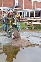 Grundschulklasse, Schulklasse legt einen Schulteich, Schul-Teich, Teich, Gartenteich, Garten-Teich im Schulgarten an, Kind füllt feinkörnigen Kies in Schubkarre, der als Bodensubstrat für den neuangelegten Teich dient