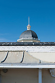 Hastings, England. Details of Victorian building; dome, cupola, flagpole, wave motif frieze and concave roof.
