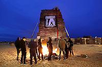 Nederland  Den Haag. 2015 12 30.  De jaarlijkse opbouw van twee vreugdevuren bij Scheveningen en Duindorp. Vorig jaar werd het wereldrecord verbroken en werd het vreugdevuur van Duindorp  opgenomen in het Guinness Book of Records. De bouwers warmen zich op bij een vuurtje