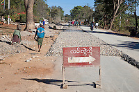 Myanmar, Burma, Shan State.  Building a Paved Road by Hand.  Laying Gravel.