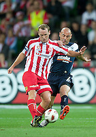 MELBOURNE, AUSTRALIA - DECEMBER 11: Kristian Sarkies of the Heart and Kevin Muscat of the VIctory compete for the ball during the round 18 A-League match between the Melbourne Heart and Melbourne Victory at AAMI Park on December 11, 2010 in Melbourne, Australia. (Photo by Sydney Low / Asterisk Images)