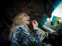 Natalia Voronkova, a volunteer who offers support and basic first aid training for Ukrainian government forces fighting Russian-backed separatists in the east of the country, puts on lipstick in the car that takes her around while she works in the Donbass region. On the roof, inside the cabin, the driver has collected military badges from the many different brigades, units and groups within the Ukrainian army.