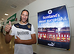 Bilel Mohsni takes delight in posing next to the Celtic shop at Glasgow airport with the Rangers slogan Scotland's Most Successful Football Club