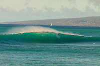 A surfer drops in as the wave crests at big Wailea with a sailboat in background, South Kohala, Big Island.