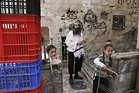 El rabino Yulish Krois junto a 3 de sus 18 hijos,  en su hogar en el barrio ultraortodoxo Mea Shearim en Jerusalén.  Krois pertenece al grupo antisionista Naturei Karta que se opone a la existencia del estado israelí, y a sus instituciones. <br /> La pandemia ha afectado fuertemente a la comunidad Haredi. El gobierno israelí decreto un confinamiento limitando la salida a 100 metros de los hogares. <br /> Foto Quique Kierszenbaum