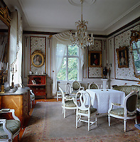 The walls of this salon are covered in floral wallpaper and decorated with gilt-framed portraits of female ancestors