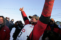 Tuesday March 13, 2007   ----   Lance Mackey, the 2007 Iditarod champion gives a victory sign to the crowd after arriving in Nome.