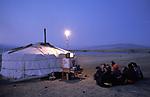 A Tsaatan herdspeople watch a video powered by a motorcycle,  on Tsaatan Uul lake,   Outer Mongolia.