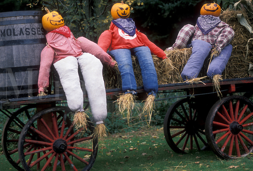 AJ4502, fall decoration, pumpkins, Vermont, A display of three scarecrows with pumpkinheads and colorful clothes sit on a wagon in Montgomery Center in Franklin County in the state of Vermont.