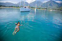Asian local woman swimming off the bow of a cruising sailboat in Hanalei Bay, Kauai