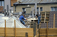 Two men repairing the roof of a building in the Goutte (18th) district of Paris, France.