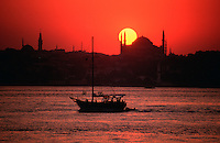 Dramatic view of a crimson sunset over the Aya Sofya (Hagia Sophia) across the Bosphorus strait. Istanbul, Turkey.