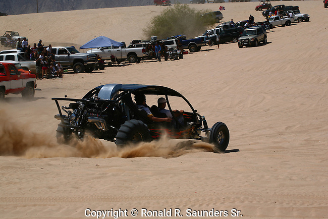 TRUCKS LINE the SAND DUNES WHILE<br />
