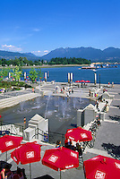 "Mill Marine Bistro - an Outdoor Restaurant Cafe with Red Sun Umbrellas - and Children playing at Water Park, along Waterfront at ""Coal Harbour"", in the ""West End"" of Vancouver, British Columbia, Canada, in Summer.  The North Shore Mountains (Coast Mountains) rise in the background."