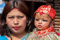Nepal, Kathmandu.  Celebrating a six-month-old boy's eating rice for the first time, his family brings him to the Ashok Binayak (Maru Ganesh) Temple for a Blessing.  He has a tilak of rice grains colored with red kumkuma powder on his forehead.