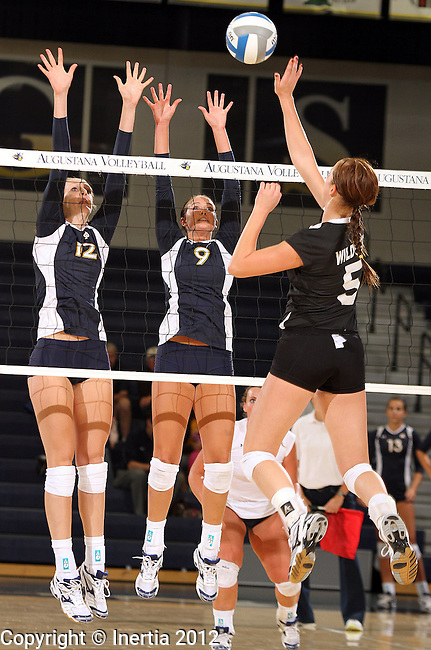 SIOUX FALLS, SD - SEPTEMBER 18:  Holly Hafemeyer #12 and Courtney Ysker #9 from Augustana team up to try and block the shot of Melanie Placke #5 from Wayne State in the first match of their game Tuesday night at Augustana. (Photo by Dave Eggen/Inertia)