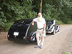 Senior man standing next to his black Camp-Inn teardrop trailer and 1936 Ford.