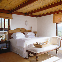 A large double bed with a wicker headboard in a guest bedroom which has a bamboo-clad ceiling